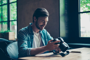 Cheerful dreamy brunet hipster traveller is watching his shoots at cafe with camera. He is a graphic designer, self employed freelancer, above top view of him sitting, in casual jeans wear