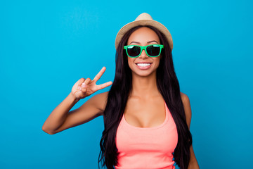 Attractive, excited carefree gorgeous traveller in trendy shiny specs, in singlet, so hot, fit and slim, relax, rest, chill mode! Showing peace gesture with fingers of her arm, long dark hair