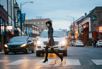 A stylish woman walking on a crosswalk at dusk