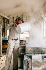 man pours maple sap into steaming evaporator