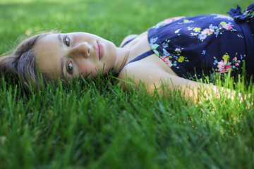 Girl Laying In A Yard Of Green Grass