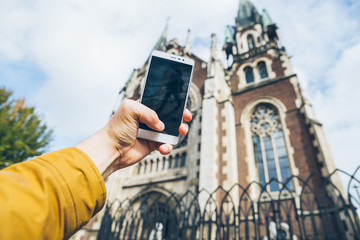 Person with smart phone makes pictures of beautiful old city