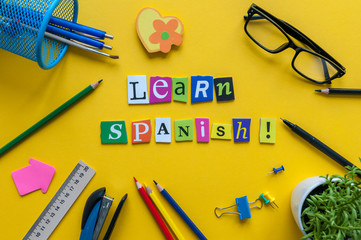 Word LEARN SPANISH made with carved letters on yellow desk with office or school supplies, stationery. Concept of Spanish language courses