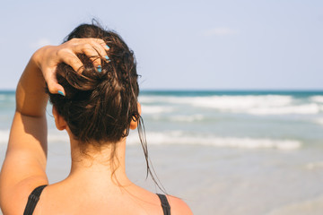 Woman holding her hair and looking at the ocean