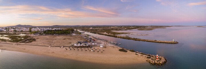Aerial dusk panoramic view at Fuseta fishing town, in Ria Formosa wetlands nature conservation park, Algarve. Portugal.