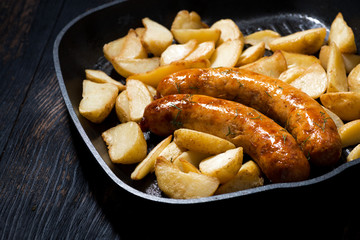 fried pork sausages with potatoes in frying pan