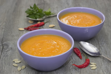 A bright cream soup of pumpkin on a gray wooden table.