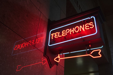 "Neon ""Telephones"" sign with a pointing neon arrow inside a building"