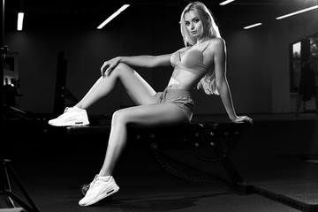 Sexy female model with long blond hair, dressed in pink fitness clothing and white sneakers, sitting on gym bench with arm put on bent leg. Attractive caucasian woman posing in sports club. Side view.