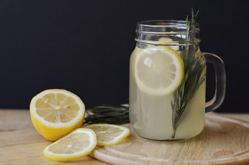 Homemade lemonade with lemon and rosemary leaves in glass jar on wooden table. Healthy drink