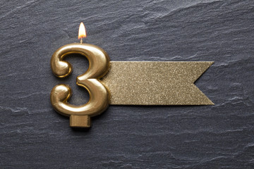 Gold number 3 celebration candle with glitter label