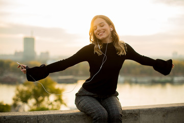 Trendy young woman listening music from smartphone outdoor