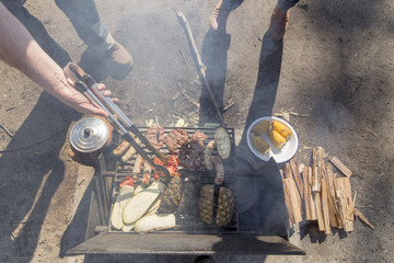 Overhead view of campfire barbecue with grey nomad couple tending meat, vegetables and fruit cooking on grill