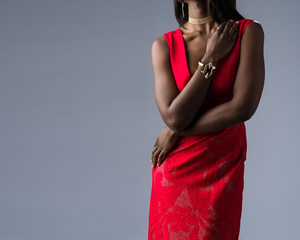Fashion model  with arm on chest in a red dress on gray background