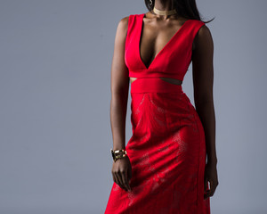 Fashion model in a red dress on gray background