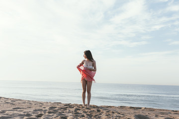 Beautiful young woman on the beach with red sarong.