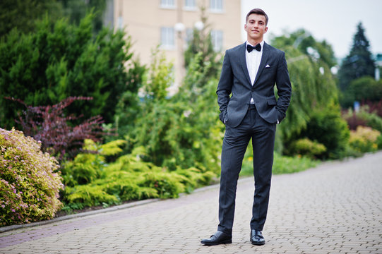 Portrait of a handsome young man in formal fancy suit posing on the pavement in the park on a prom day.