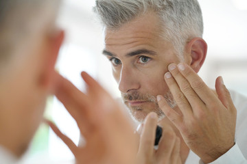 Middle-aged man applying cosmetic on his face, mirror view
