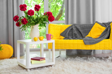 Interior of beautiful light modern room with peony flowers on table