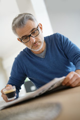 Middle-aged man at home drinking coffee and reading newspaper