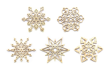 Laser cut wood snowflakes ornaments isolated on white background. Set of five different wooden snowflakes.