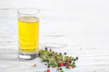 Glass with oil and condiments on light wooden background