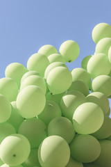 Bunch of Helium-Filled Green Balloons Against Blue Sky