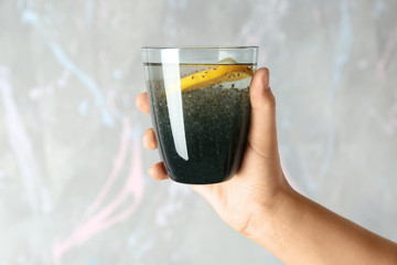 Hand holding glass of water with chia seeds and lemon on light background
