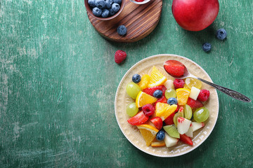 Plate with delicious fruit salad on table