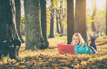 Young woman with computer lies on a yellow leaves