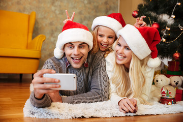 Happy little girl in Santa's hat makes horns to her parents while her father taking Christmas photo on mobile phone