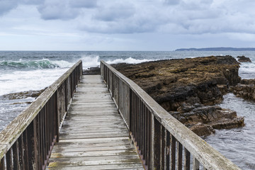 Wooden footbridge on the coast of Northern Ireland in a cloudy day