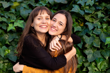 Outdoor portrait of two happy sisters in a park
