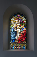 Stained-glass window inside church showing Christian scene.