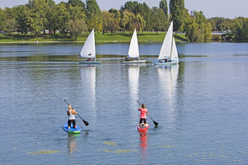 Two women on paddle board and three boat sailling in lake