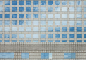 Pettern of the windows of a building reflecting clouds