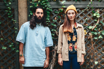 Portrait of young hipster couple on ivy background.