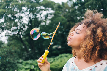 Girl with big afro having blowing bubbles in the park