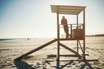 Young man posing on the lifeguard post