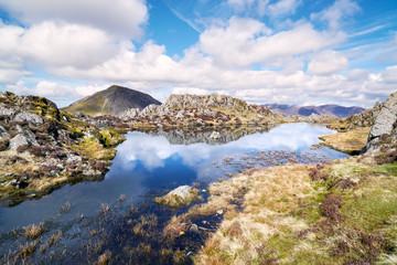 Views of the summit of High Crag and reflections of the sky in a mountain tarn from the summit of Hay Stacks in the English Lake District.
