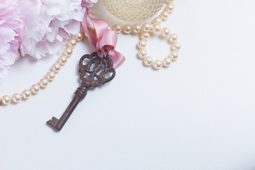 Skeleton key with peony flowers, glamour bottle and jewellery close up - love and wedding concept