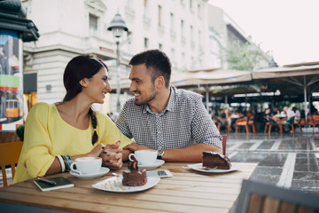 Smiling Couple in Love Sitting at a Cafe