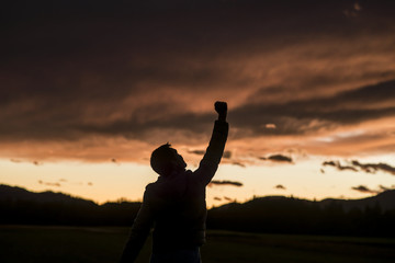 Jubilant man raising his fist against a sunset