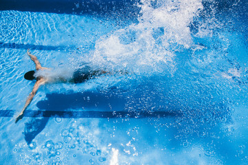 Young man jumping into a pool