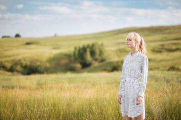 Blonde woman standing in a field looking into the distance