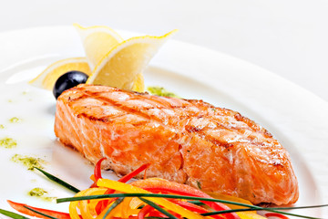 Grilled salmon with lemon on a white plate.