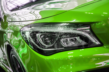 The headlamp of a green sports car of aggressive form with a part of the hood and black wheel,...