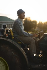 Side view of farmer sitting on tractor