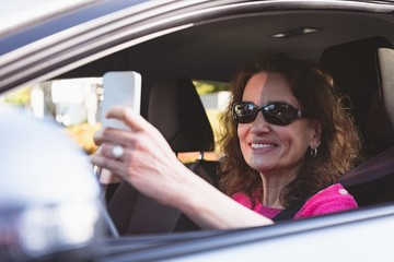 Woman using mobile phone while driving car