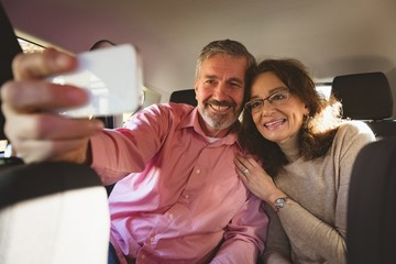 Couple taking selfie in car